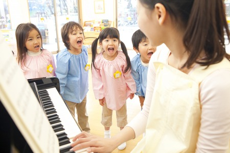 Kindergarten children singing to fit the piano of kindergarten teachers Stock Photo