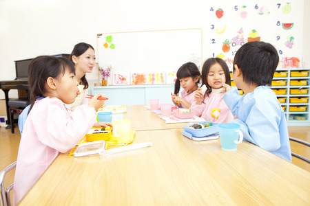schooling: Kindergarten teacher eats lunch and kindergarten children Stock Photo
