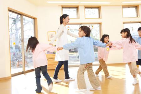 educators: Los maestros de kindergarten y niños de jardín de infantes que bailan en un círculo