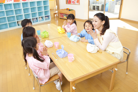 kinder: Maestra de Kindergarten come el almuerzo y los niños de jardín de infantes