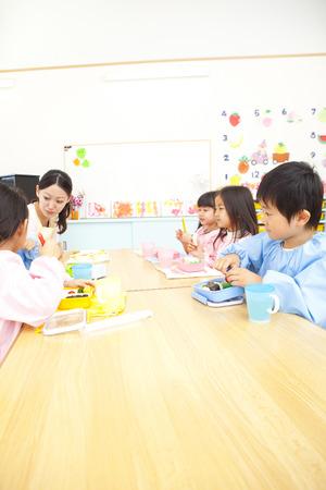 kindy: Kindergarten teacher eats lunch and kindergarten children Stock Photo