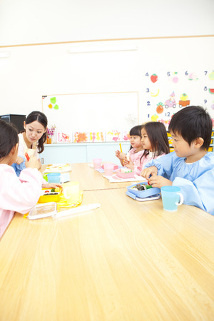 smocking: Kindergarten teacher eats lunch and kindergarten children Stock Photo