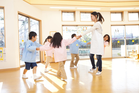 Kindergarten teachers and kindergarten children dancing in a circle 免版税图像