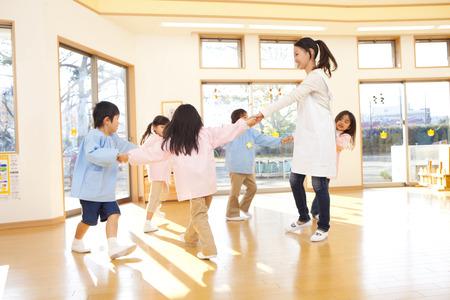 Los maestros de kindergarten y niños de jardín de infantes que bailan en un círculo Foto de archivo - 43748874