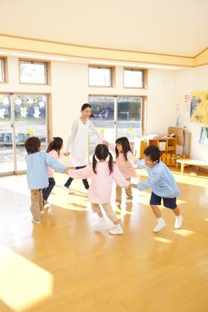 kinder: Los maestros de kindergarten y niños de jardín de infantes que bailan en un círculo
