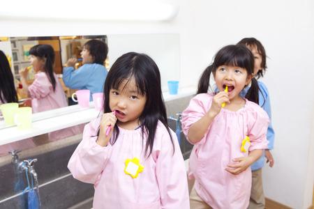Tooth brushing to kindergarten children photo