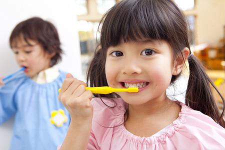 mujer hijos: Cepillado de dientes a los niños de jardín de infantes