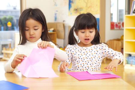 kindergartener: Folding origami nursery girls
