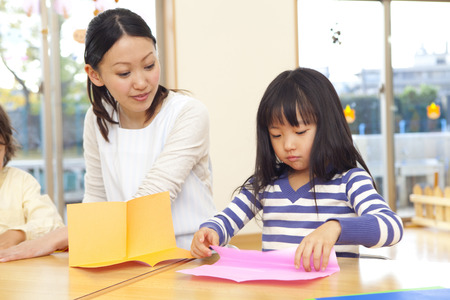 Nursery and preschool girls folding origami Stock Photo