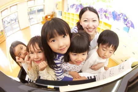 female kid: Nursery school children and nursery teacher smiling in front of the piano Stock Photo