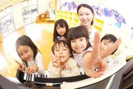 保育園学童・保育ピアノの前に笑みを浮かべて