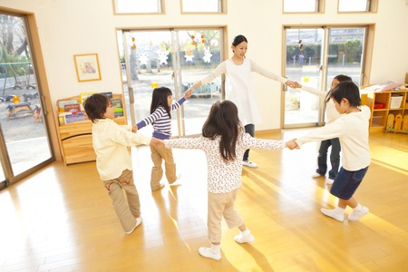 Nursery teacher and nursery school children dancing in a circle Standard-Bild