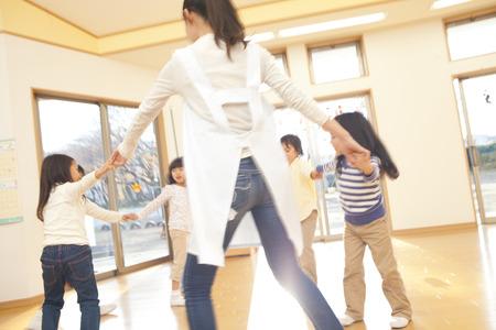 kindy: Nursery teacher and nursery school children dancing in a circle Stock Photo