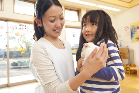 kindy: Nursery school girls and nursery teacher who holds a guinea pig