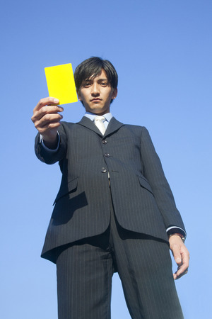 yellow card: Businessman with a yellow card Stock Photo