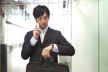 Businessman to check the time while the phone