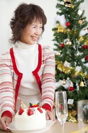 weihnachtskuchen: Senior woman carrying a Christmas cake