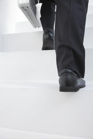 satisfactory: Feet of businessman climbing stairs