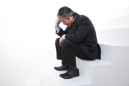 sluggish: Businessman sitting on the stairs, falling Stock Photo