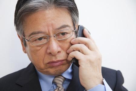 mature business man: Businessman to phone smartphone