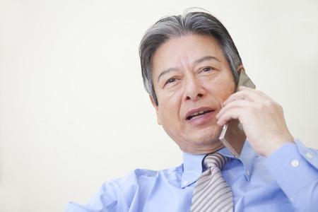 ビジネスマンが携帯電話で話しています。