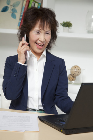 exert: Businesswoman to phone while using a laptop