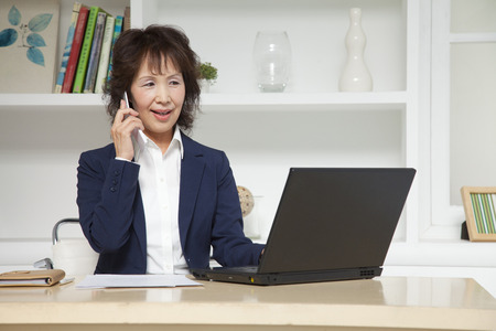 Businesswoman to phone while using a laptop