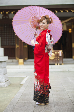 early 20s: Umbrella smiling furisode kimono woman Stock Photo