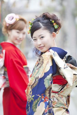 2 women of kimono wearing that smile looking back