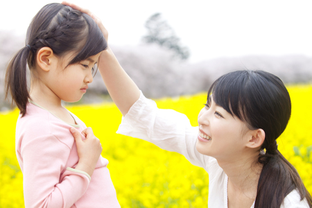 appease: Mother soothing a child in a rape field Stock Photo