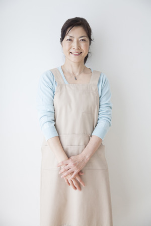 momma: Housewife smile and leaning on the wall Stock Photo