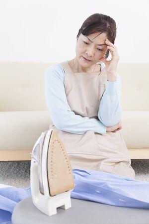 tiring: Housewife tiring to ironing