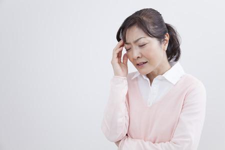 真ん中の女性は頭痛に苦しむ 写真素材