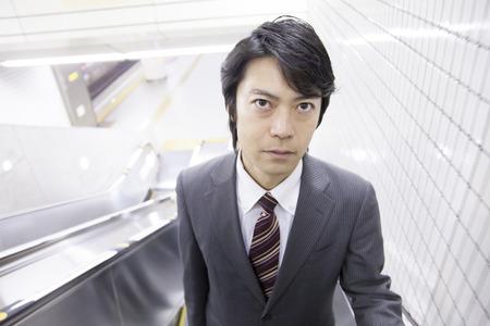 to go up: Businessman go up the subway escalator Stock Photo