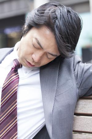 ベンチで寝ているビジネスマン