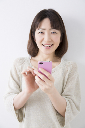 Middle woman smiling with a smartphone