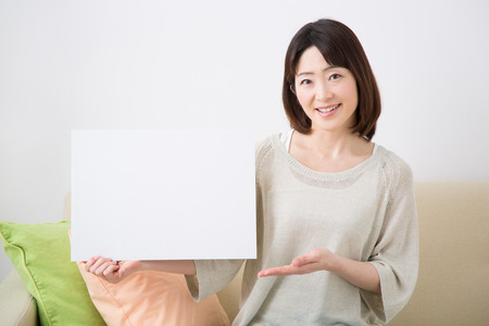 message board: Middle woman smiling with a message board