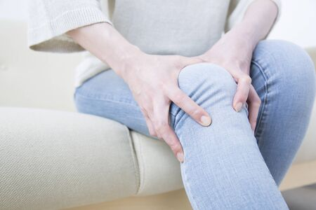 Middle woman suffering from pain in the knee Stock Photo
