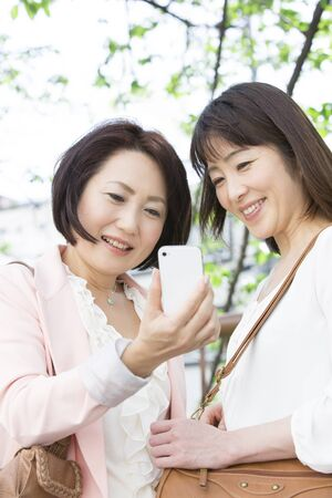 shopping buddies: Middle women who see the Smartphone Stock Photo