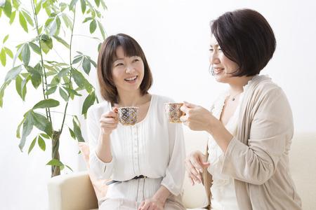 コーヒーを飲みながらチャット中の女性 写真素材