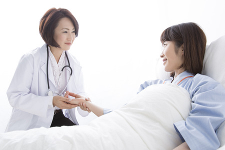 asian hospital: Female doctor and the patient to take the pulse