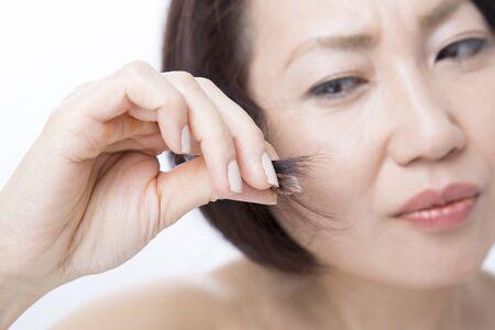 枝毛を心配する中間の女性 写真素材