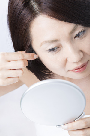 灰色の髪を心配する中間の女性 写真素材