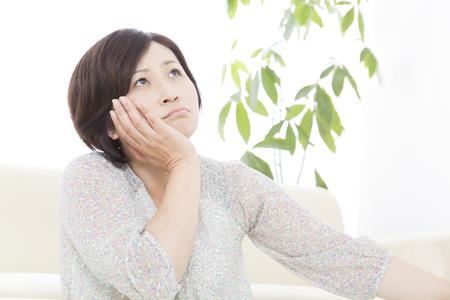 月の肘に苦しんでいる中間の女性