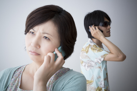 con man: Middle women undergoing suspicious phone Stock Photo