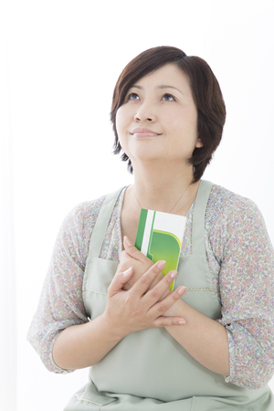passbook: Housewife ruminate and holding a passbook to the chest Stock Photo