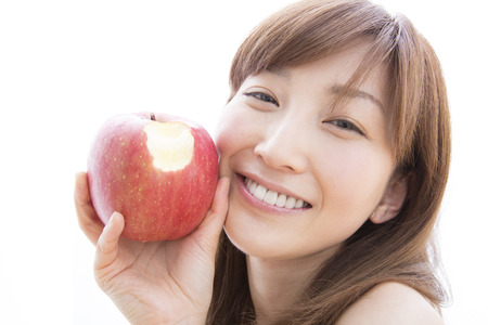 Woman smiling with a bite apple