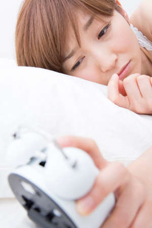 early 30s: Women see the alarm clock Stock Photo