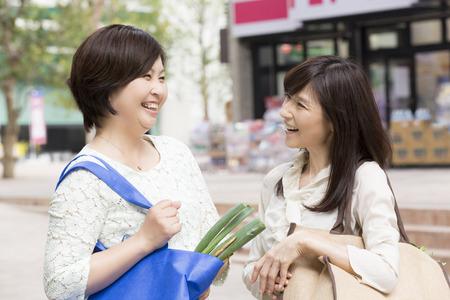 2 つの中央女性はスーパーの前でチャット 写真素材