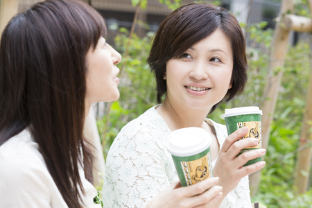 Two middle woman drinking coffee